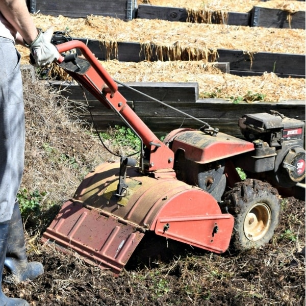 rotor tiller digging in ground. Essential Garden Tools All Gardeners Need. Hidden Springs Homestead