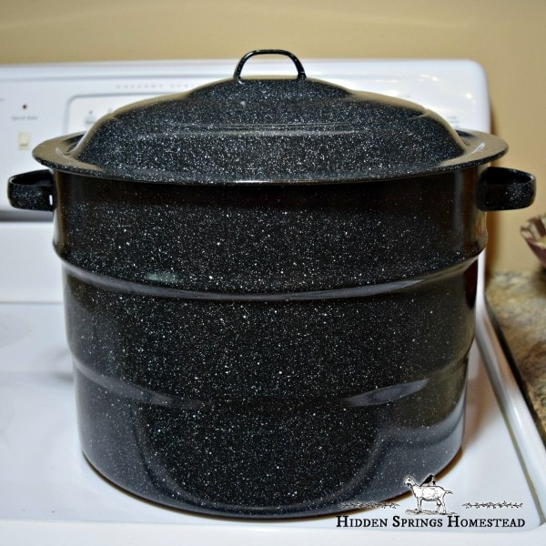 Black waterbath canner sitting on a white stove
