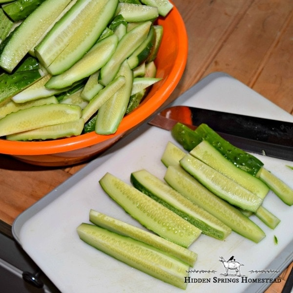 Sliced cucumbers laying on a white cutting board with a knife getting them ready for canning dill pickles