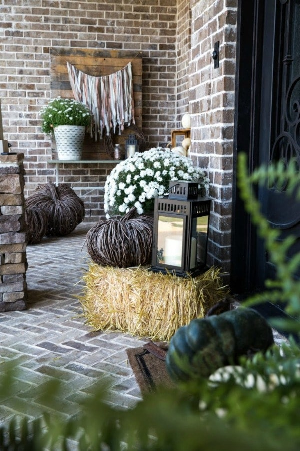 Cozy up your fall porch decor using metal buckets, natural pumpkins, and white mums. This simple and easy fall porch decor is ideal for the rustic decor at heart.